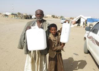 水を運ぶためのポリタンクを受け取った老人と少年.JPG